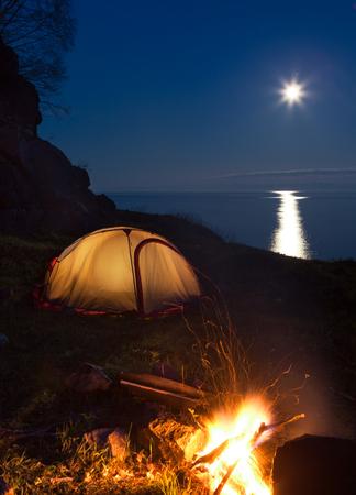Tent and campfire near lake at moon night Stockfoto