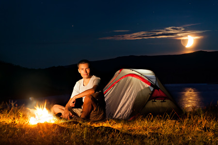 Hiker have a rest in his camp at night near campfire