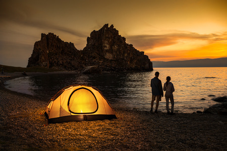 Couple stand at tent and Baikal lake shore and looking at the sunset