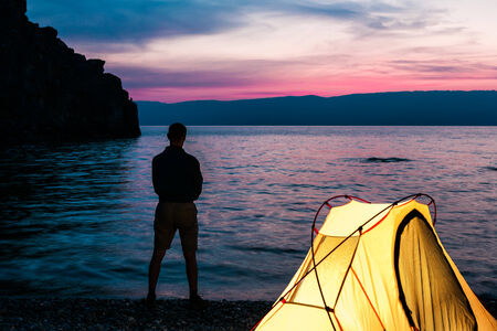 Man stand close to tent and lake shore and looking at sunset