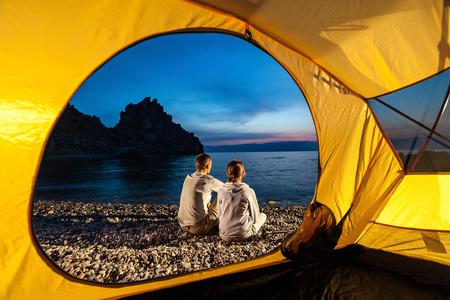 Man and woman sit near tent at lake shore and look at sunset