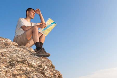 Hiker sits on rock against blue sky and holds map photo