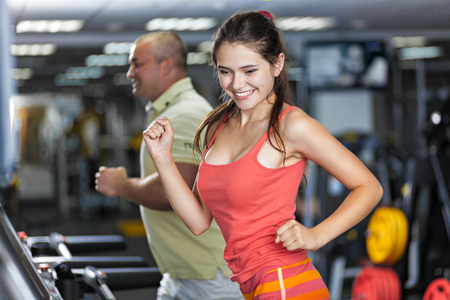 Sportive woman and man are running on treadmill in a gym photo