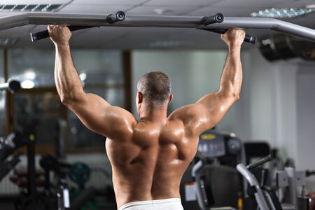pullups: Strong man doing pull-ups on a bar in a gym