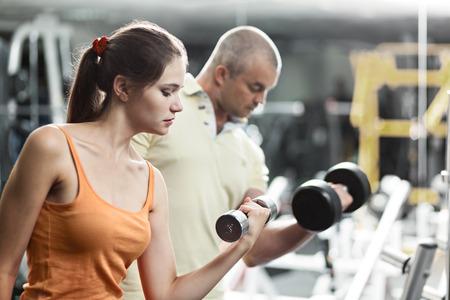 aide � la personne: Femme au club de sant� avec son entra�neur personnel, l'apprentissage de la forme correcte avec halt�res Banque d'images