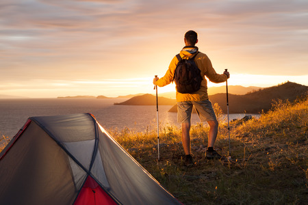 Man looking at beautiful sunrise at big lake near tent Imagens