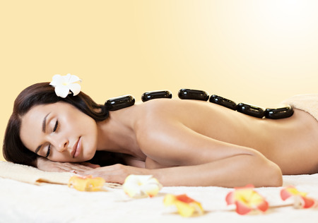 portrait of young beautiful woman in spa environment  Black stones on her back photo