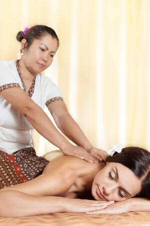 Thai massagist doing massage for european woman in spa salon Stock Photo