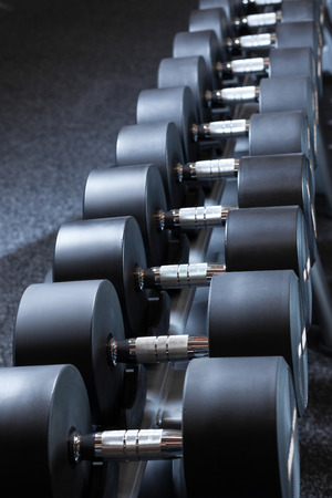 Many dumbbells are on stand at the gym Stock Photo