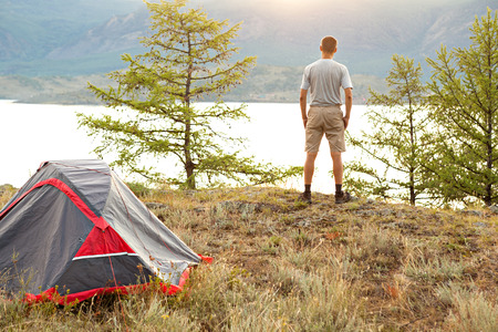 Man looking at beautiful sunrise at big lake near tent photo