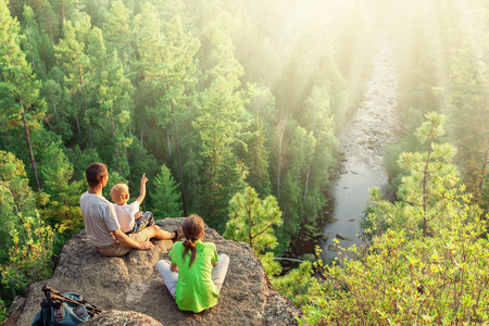 Family with backpacks sit on big rock above green forest and look at river Stock Photo