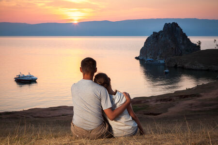 Two tourists looking at beautiful view of Baikal lake photo