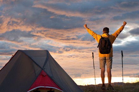 Man looking at beautiful sunrise near tent arms raised photo