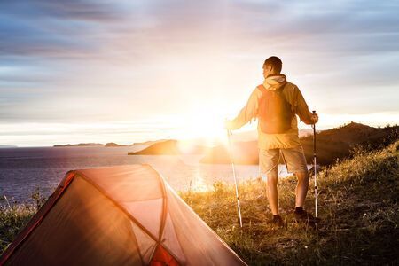 Backpacker looking at beautiful sunrise at big lake near tent photo