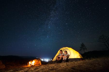 fogatas: Pareja de turistas de senderismo tiene un descanso en su campamento por la noche cerca de la hoguera