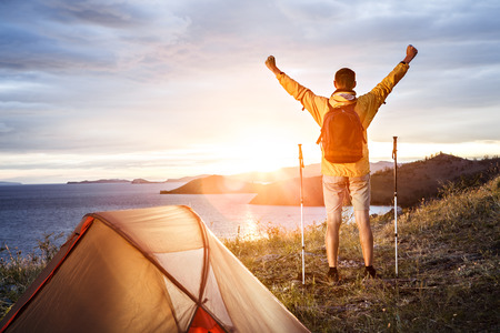 Backpacker with arms raised looking at beautiful sunrise at big lake near tent photo