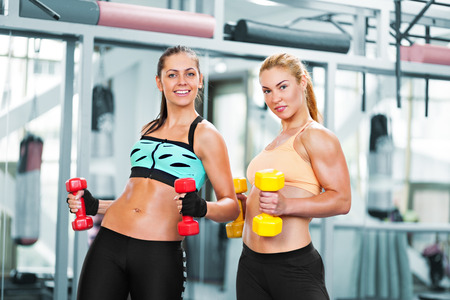 Two portive young women doing exercise with barbells in the gym photo