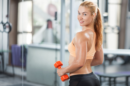 Sportive young woman doing exercise with barbell in the gym photo