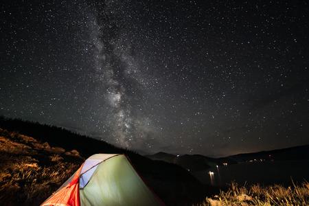 Illuminated tent at night under night stars.