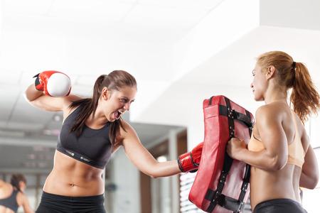 Two young pretty women boxing photo
