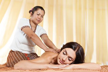 Thai massagist doing massage for european woman in spa salon photo