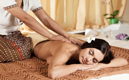 face massage: Thai massagist doing massage for european woman in spa salon Stock Photo