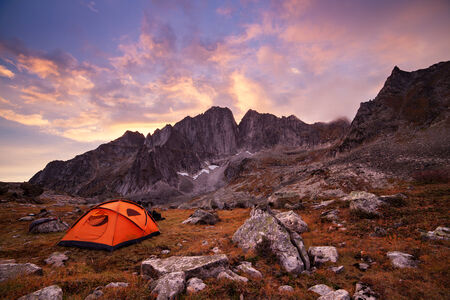 Tent in mountains at beautiful sunrise photo