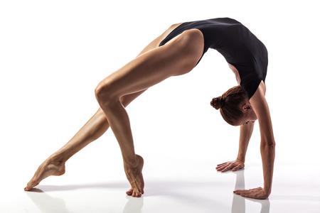 Young girl doing gymnastics bridge isolated over white