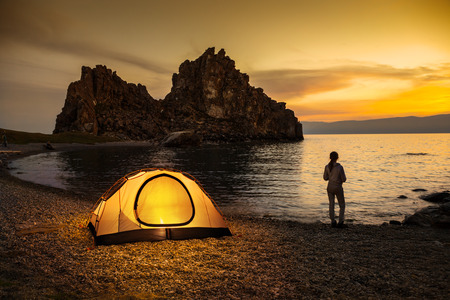 camping: Tourist stand near tent and lake shore and looking at the beautiful sunset Stock Photo