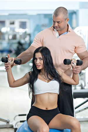 fitness couple: Woman at the health club with her personal trainer, learning the correct form with barbell