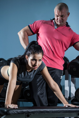 bilding: Woman at the health club with her personal trainer, learning the correct form Stock Photo