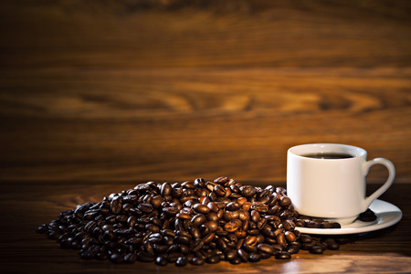 cup of coffee: Coffee cup and coffee beans on old wooden background Stock Photo