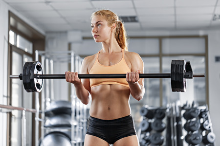 Sportive young woman doing exercise with barbell in the gym Фото со стока