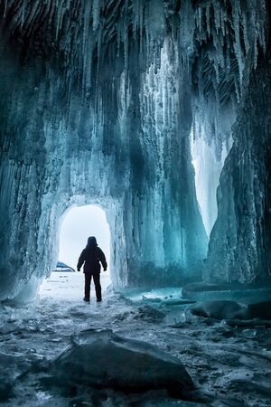 snow  ice: Man in front of a large ice cave and looking into the distance Stock Photo