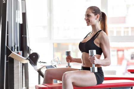 bilding: Sportive young woman doing exercise with barbell in the gym Stock Photo