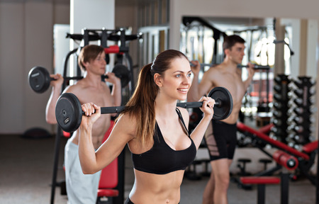 exercise weight: Group of three people do cross fit in the gym