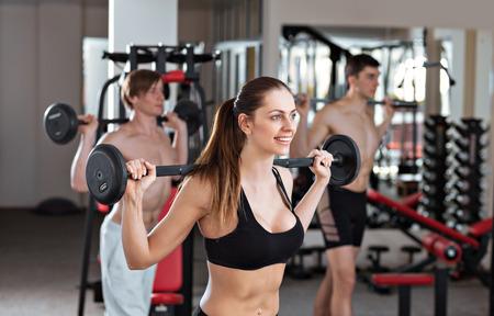 levantar peso: Grupo de tres personas no cruzar en forma en el gimnasio
