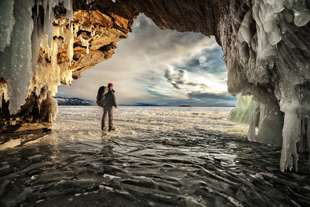 Backpacker across the ice cave and looking at sunrise