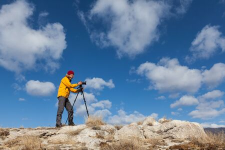Photographer is taking picture using tripod against cloudy sky Фото со стока