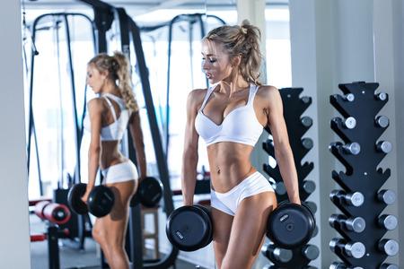 silhouette femme: Jeune femme soulevant des haltères sexy dans la salle de gym Banque d'images