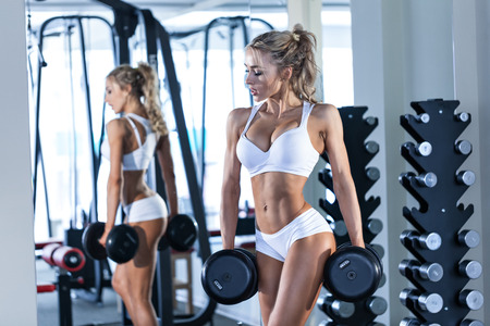 Young sexy woman lifting dumbbells in the gym