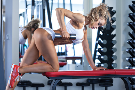 fitness club: Sportive young woman doing exercise with barbell in the gym Stock Photo