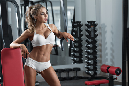 Young sexy woman dressed in white clothes in the gym Stock Photo