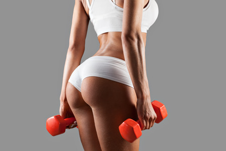 Strong sexy woman is training with dumbbells on gray background