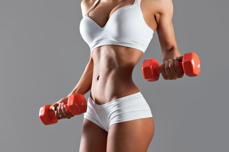 Torso of a young sexy woman lifting dumbbells on gray background Stockfoto