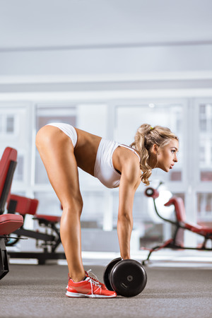 Sportive young woman doing exercise with barbell in the gym Stock Photo