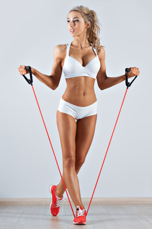Sportive young woman doing exercise with skipping rope in the gym