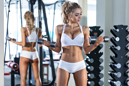 Young sexy woman in white sportwear lifting dumbbells in the gym