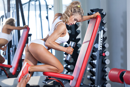Sportive young woman doing exercise with barbell at the gym Stock Photo