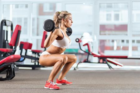 Sportieve vrouw die kraken met een halter in de sportschool